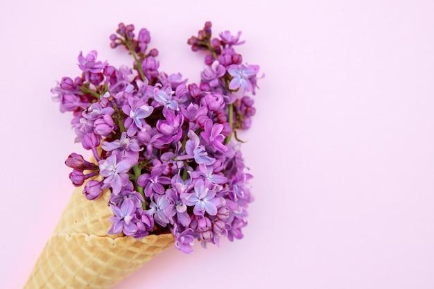 Fiori lilla in un cono gelato su uno sfondo rosa.
