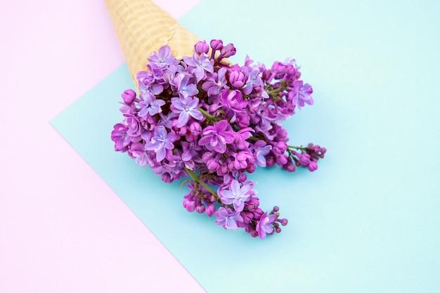 Fiori lilla in un cono gelato su uno sfondo rosa-blu.