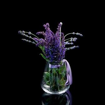 Fiori lilla con foglie verdi in un vaso su fondo nero