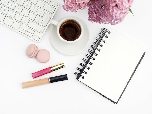 Fiori lilla sull'ufficio domestico femminile della scrivania con vista superiore del fondo bianco del caffè e della tastiera