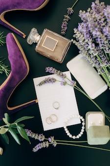 Scarpe tacco alto lilla una bottiglia di profumo uno smartphone gioielli e fiori su una superficie verde