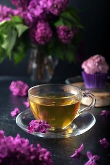 Fiori di lillà, una tazza di tè con muffin con crema di formaggio cremoso