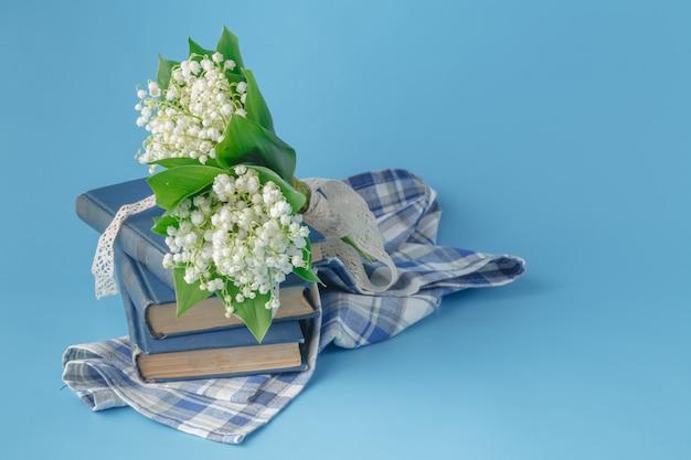 Mughetti e libri su sfondo blu