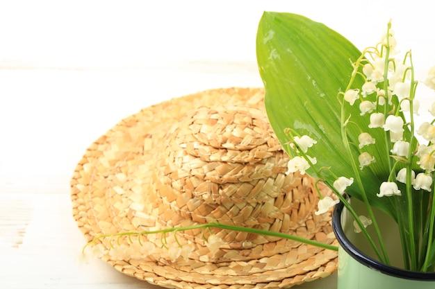 Mughetti in una tazza di smalto con un cappello di paglia su uno sfondo di legno bianco