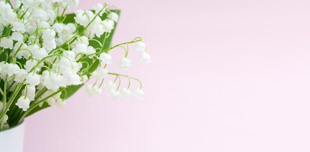Il mughetto fiorisce in un vaso su uno sfondo rosa.
