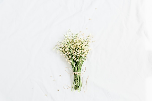 Fiori di mughetto su sfondo bianco. flatlay, vista dall'alto