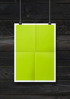 Poster piegato verde lime appeso a una parete di legno nera con clip.