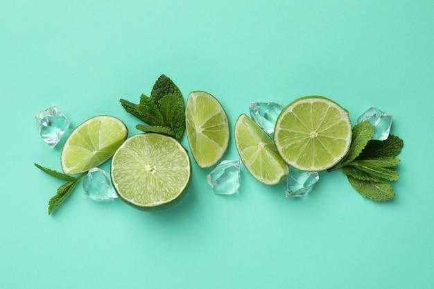 Fette di lime, cubetti di ghiaccio e foglie di menta su sfondo di menta
