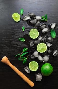 Limette, foglie di menta e cubetti di ghiaccio sul nero. ingredienti per il cocktail mojito.