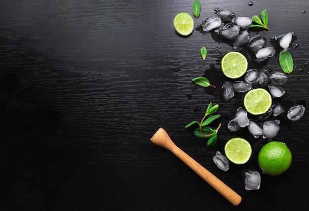 Limette, foglie di menta e cubetti di ghiaccio sul nero. ingredienti per il cocktail mojito
