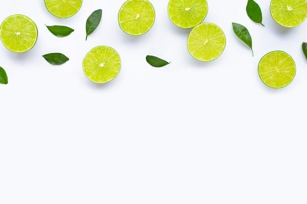 Limette con foglie isolati su sfondo bianco.