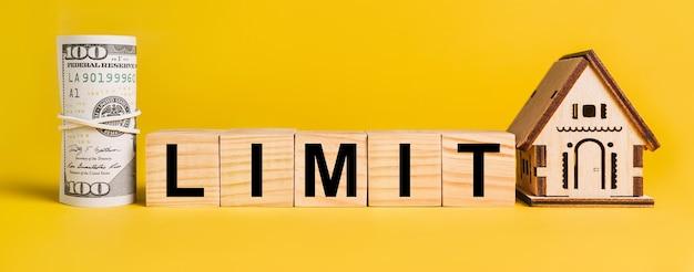 Limite con il modello in miniatura della casa, soldi su un giallo. concetto di affari, finanza, immobiliare, casa