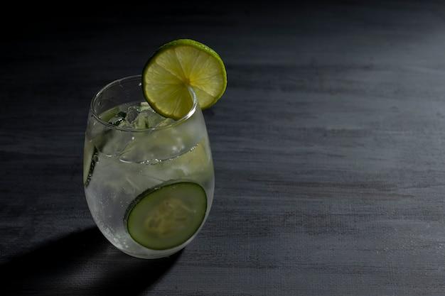 Limonada con agua mineral hielos y unas rodajas de pepino en el interior sobre una mesa vintage
