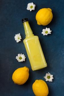 Bottiglia di limoncello con limoni e fiori su sfondo blu vista dall'alto