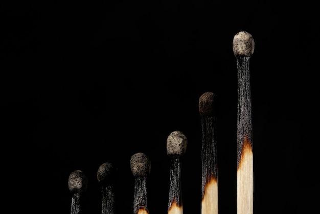 Linea di fiammiferi bruciati a forma di un grafico imminente sullo sfondo scuro