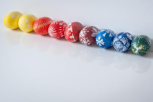 Linea di uova di pasqua su sfondo bianco con riflessione. concetto di vacanza di pasqua.