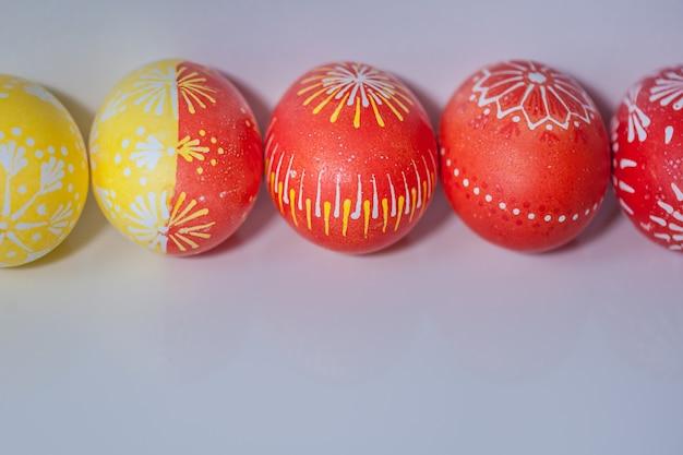 Linea di uova di pasqua su sfondo bianco con riflessione.