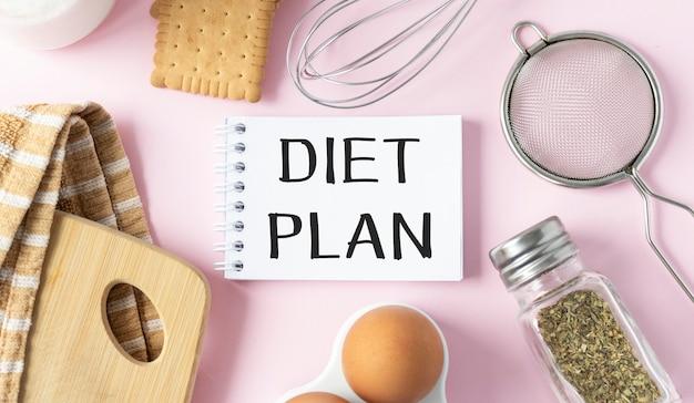 Blocco note di linea con il testo dell'elenco del piano dietetico sul tagliere con forchetta e cucchiaio di legno e nastro di misurazione sul tavolo rosa, ricette alimentari o piano dietetico per abitudini sane concetto di nota
