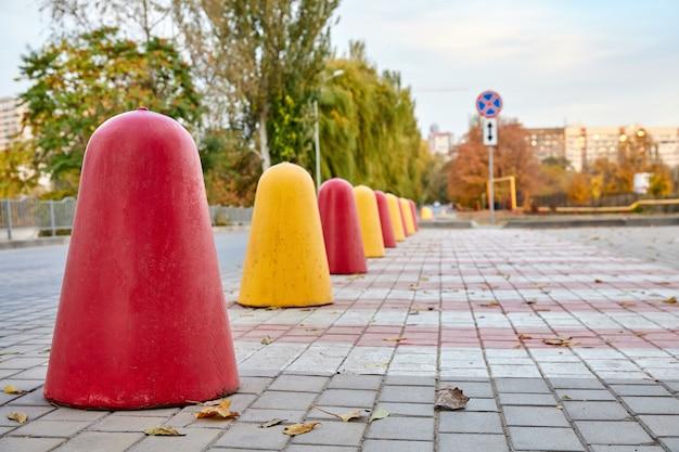 Linea di coni stradali in cemento rosso e giallo per deviare il traffico
