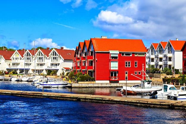 Una fila di case bianche a due piani vicino al porto
