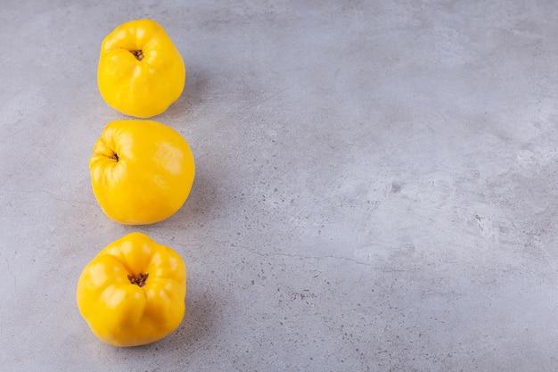Linea di frutti di mela cotogna freschi interi maturi posti su uno sfondo di pietra.