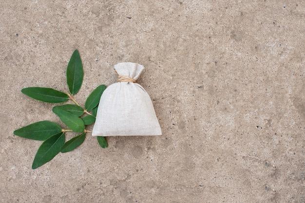 Borsa di lino su una superficie di cemento con foglie