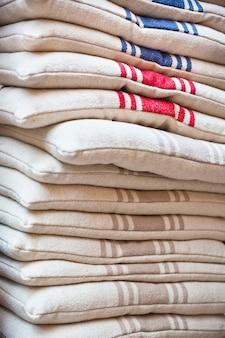 Pila di cuscini per sedie in lino. colpo esterno verticale.