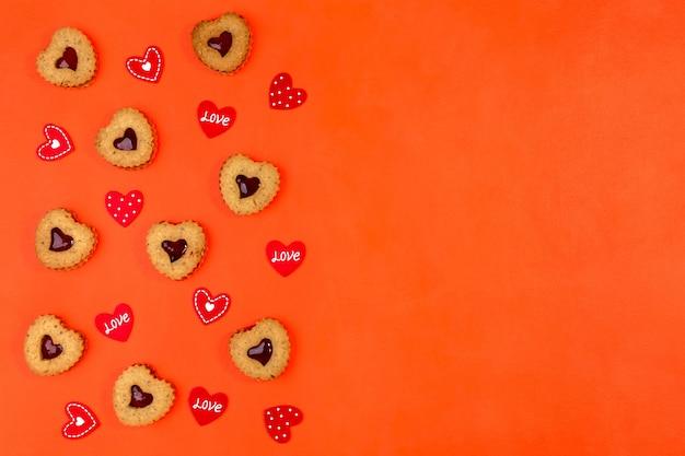 Biscotti linzer a forma di cuore e san valentino su fondo rosso con copia dello spazio
