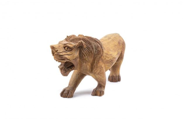 Leone scolpito in legno duro isolato su un muro bianco.