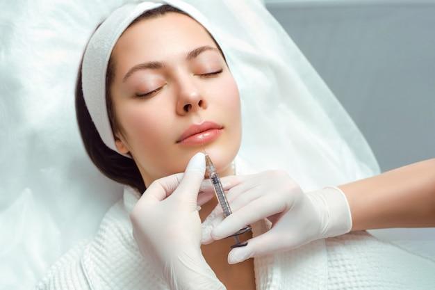 Procedura di aumento e correzione delle labbra in un salone di cosmetologia. lo specialista fa un'iniezione