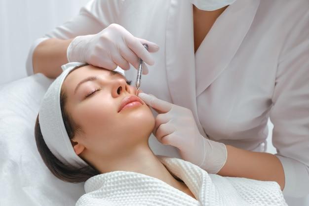Aumento delle labbra e procedura di correzione in un salone di cosmetologia lo specialista fa un'iniezione