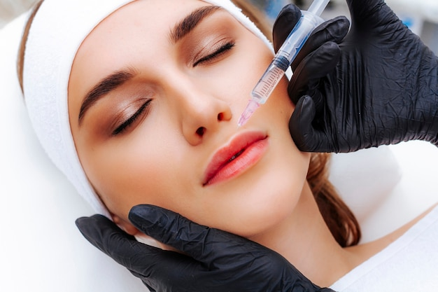 Procedura di aumento delle labbra con acido ialuronico. l'estetista perfora le labbra con un ago. iniezione sottocutanea.