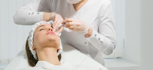Procedura di correzione della forma delle labbra in un salone di cosmetologia. lo specialista fa un'iniezione sulle labbra
