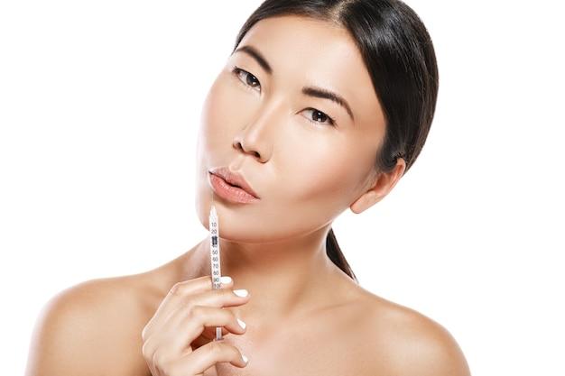 Procedura di aumento delle labbra. la donna asiatica con la siringa è pronta per l'iniezione del riempitivo.