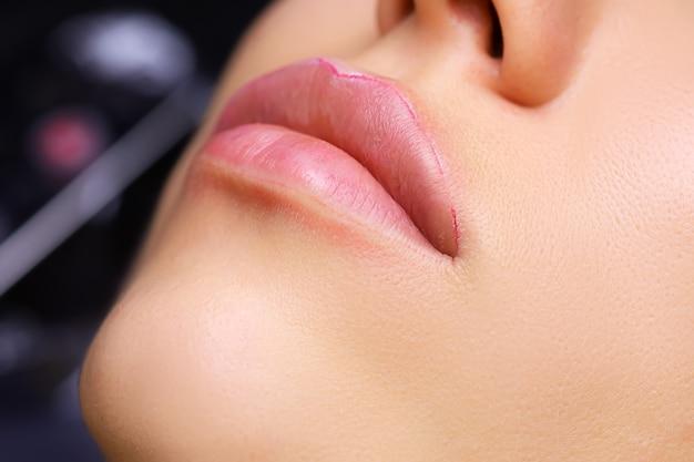 Primo piano delle labbra del modello, su cui è già stato tatuato il contorno delle labbra, è stata applicata l'anestesia sul contorno delle labbra, una striscia bianca è visibile dal fondo delle labbra