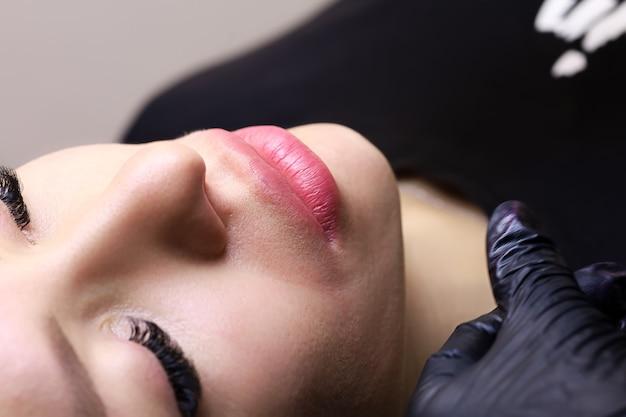 Labbra di una modella in primo piano con un tatuaggio sulle labbra, lavoro finito