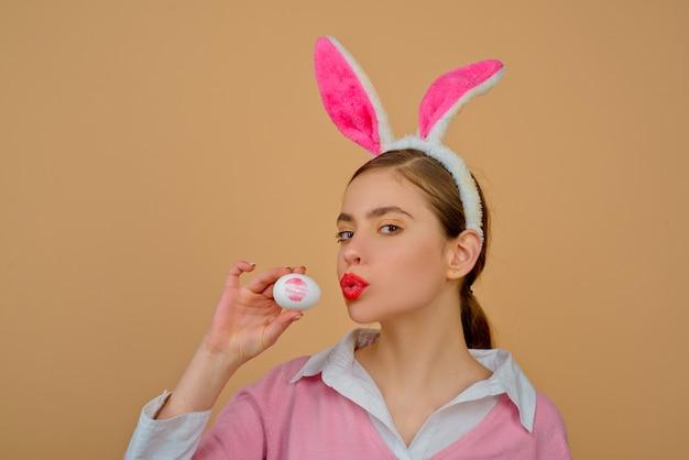 Labbra e pasqua, impronta di bacio del rossetto sull'uovo di pasqua. buona pasqua. giovane donna in orecchie da coniglio coniglietto.