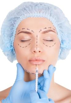 Miglioramento delle labbra. attraente giovane donna in copricapo medico e schizzi sul viso tenendo gli occhi chiusi mentre i medici le fanno un'iniezione nelle labbra