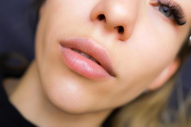 Labbra di una ragazza modello prima della procedura di trucco permanente delle labbra