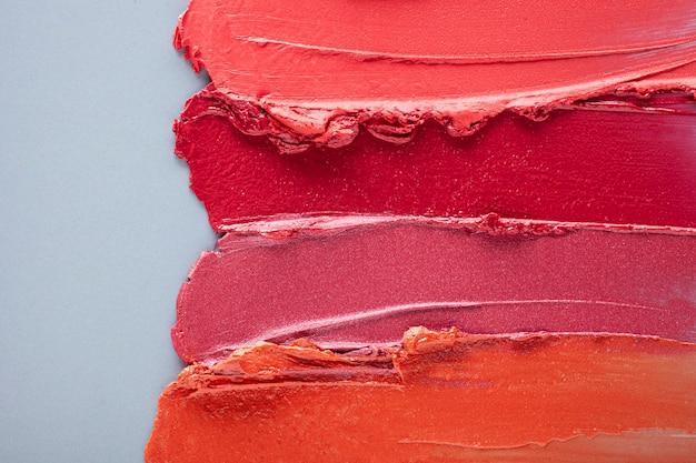 Campione di sfumino rosa rosso corallo di rossetto su sfondo colorato grigio blu