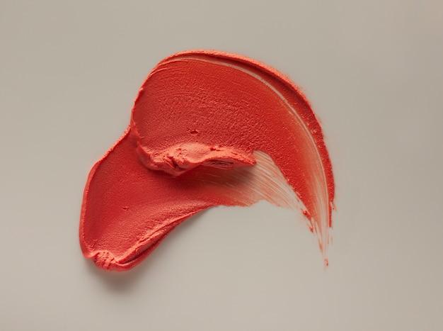 Campione di macchie di rossetto arancione marrone su sfondo colorato grigio beige