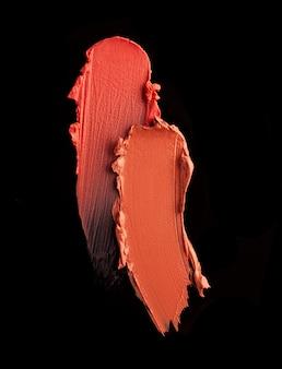 Campione di macchie di rossetto arancione su sfondo nero