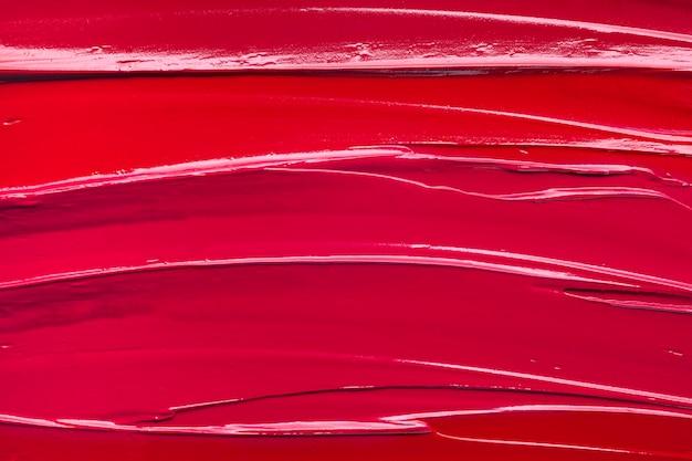 Fondo rosso di struttura dell'onda della macchia di rossetto