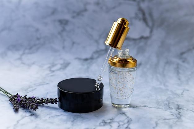 Collagene liquido o acido ialuronico con pipetta in bottiglia di vetro, su fondo in marmo