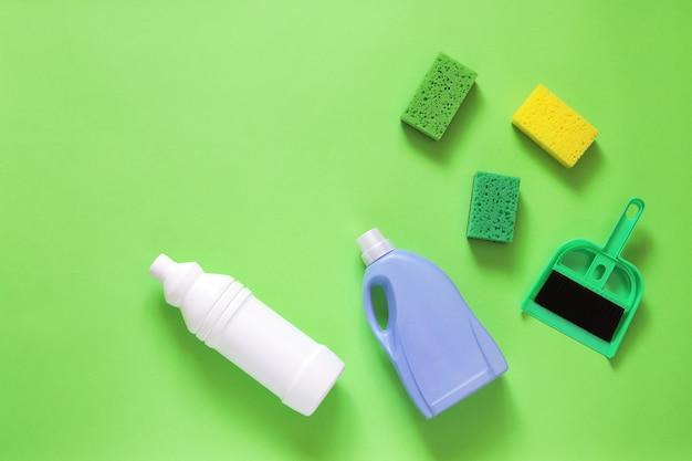 Detergenti liquidi in bottiglie di plastica, spugne e scopa per la pulizia della casa, vista dall'alto