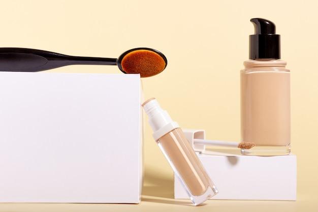 Fondotinta liquido in flacone su supporto, pennello da trucco e correttore. correttore viso su sfondo beige con copia spazio. modello di imballaggio con spazio di copia