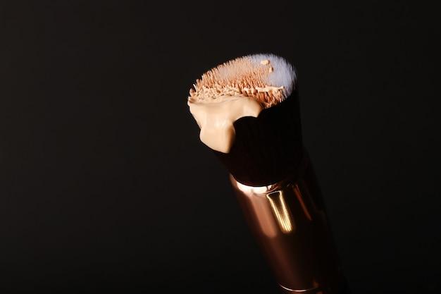 Fondotinta liquido adagiato sul pennello da trucco per il contouring. fondotinta cosmetico per il viso di bellezza, strumento per un trucco perfetto. gocciolamento di crema bb o correttore, su sfondo nero. concetto di cosmetici.