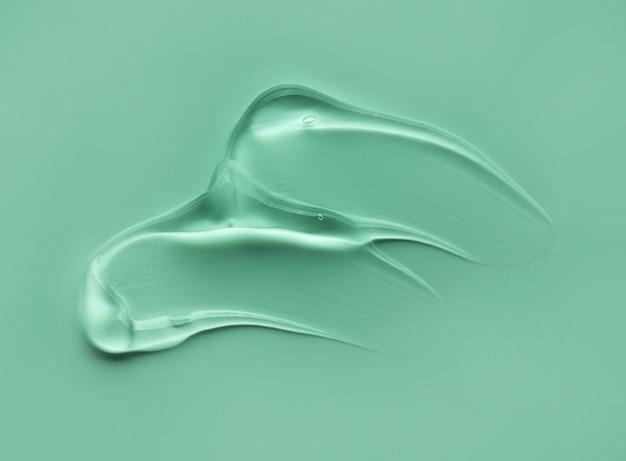 La macchia cosmetica del gel liquido cade il fondo grigio verde di struttura