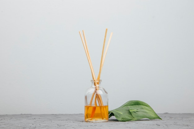 Fragranza liquida per ambiente con bastoncini aromatici in flacone di vetro Foto Premium