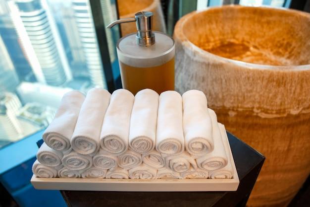Bottiglia di sapone liquido e asciugamano sulla vasca nel bagno moderno a casa, hotel